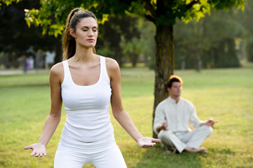 Young couple meditating in park