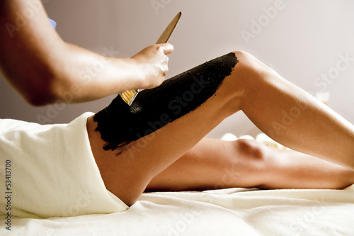 Young woman getting a mud treatment on leg