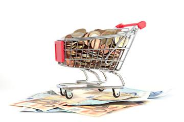 Einkaufswagen mit Euromünzen auf Euroscheinen auf weiß isoliert