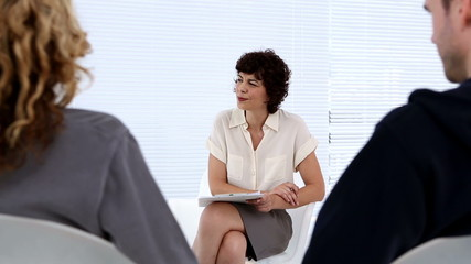 Therapist listening to group of patients