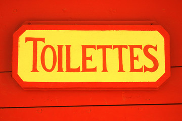 Ancient toilet sign on red wooden background