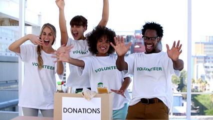 Group of cheerful volunteers raising their arms