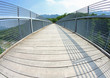 bridge with a wooden walkway and handrail made of galvanized ste