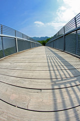 long bridge with a wooden walkway and handrail made of galvanize