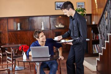 Kellner bringt Mann einen Kaffee