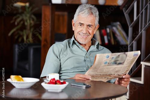 Senior beim Frühstück mit Zeitung