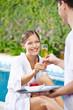 Frau trinkt Sekt am Pool eines Hotels