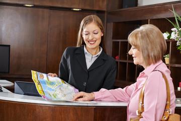 Seniorin in Hotel schaut auf Stadtplan
