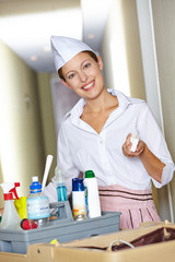 Zimmermädchen schiebt Reinigungswagen mit Reinigungsmitteln