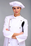 Portrait of young woman chef on grey background