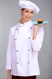 Portrait of young woman chef with cake on grey background