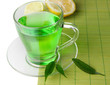 Transparent cup of green tea with lemon