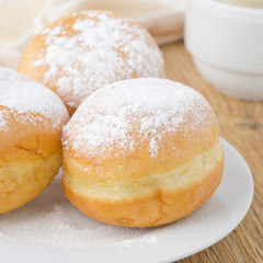 three donuts sprinkled with powdered sugar