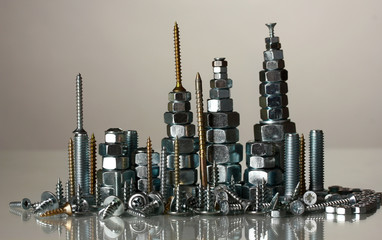 Many types of metal bolts, screws and nuts on grey background