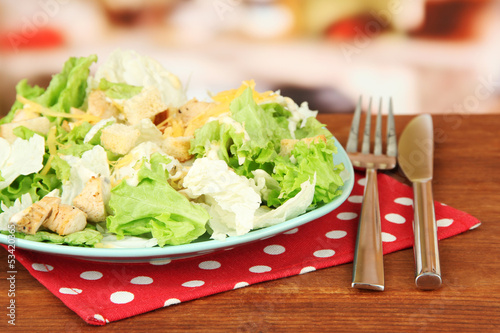 Caesar salad on blue plate, on bright background