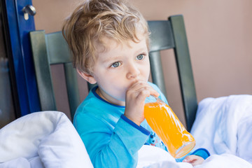 Happy little boy drinking orange juice on balcony