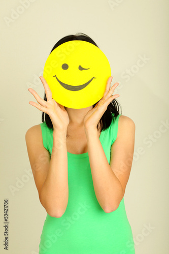 Young woman holding paper with happy smiley on gray background.