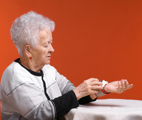 Old woman measures arterial pressure
