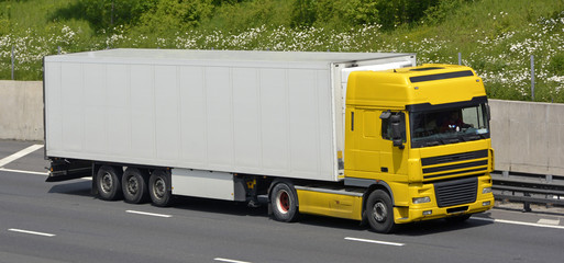 Yellow heavy goods vehicle truck and trailer on M25 motorway