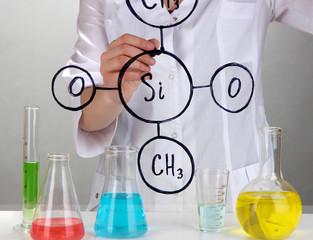 Chemist woman writing formulas on glass on grey background