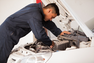 Young mechanic working on a car engine at an auto shop