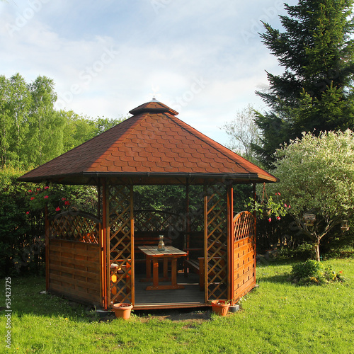 Wooden summerhouse is in a morning garden