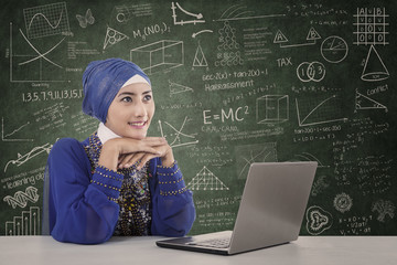 Beautiful female muslim study with laptop at classroom