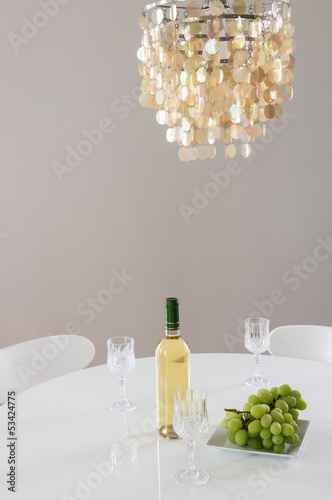 Decorative chandelier and bottle of wine on the table