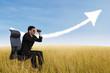 Businessman using binoculars looking at growing chart cloud