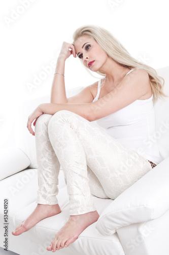 Nachdenkliche oder traurige junge blonde Frau in Weiß