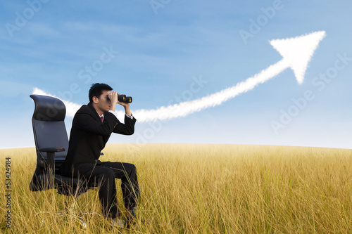 Businessman using binoculars looking at growing chart cloud