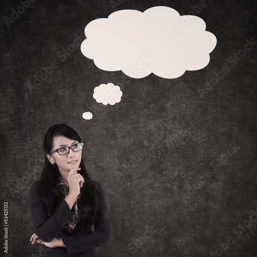 Businesswoman thinking and cloud copyspace