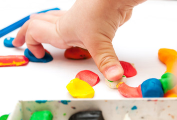Child moulds from plasticine on table, hands with plasticine