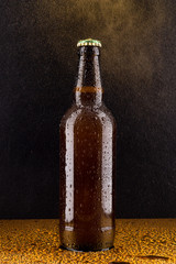 Cold brown beer bottle on black