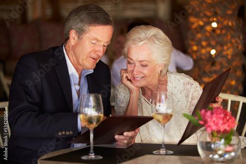 Senior Couple Choosing From Menu In Restaurant - 53428104
