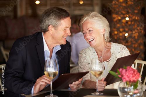 Leinwanddruck Bild Senior Couple Choosing From Menu In Restaurant