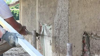 Men shooting spray plaster on a building wall