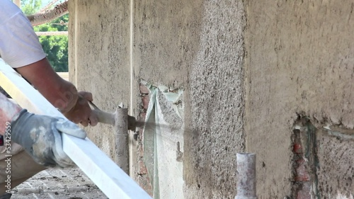 Men shooting spray plaster on a building wall