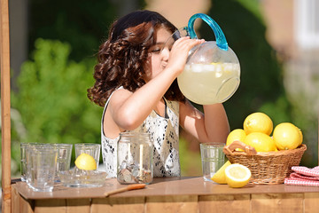 little girl drinking from lemonade pitcher