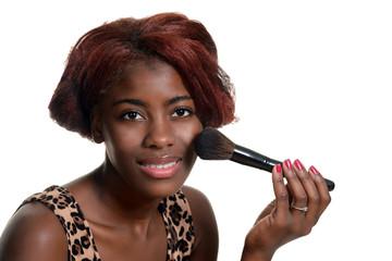 young black woman putting on blush makeup