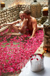 Couple Relaxing In Flower Petal Covered Pool At Spa