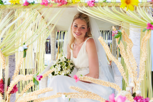 Bride Sitting Under Decorated Canopy At Wedding