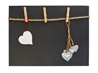 Schiefertafel mit Leine, Klammern und Herzen