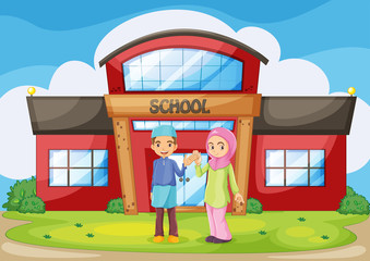 A muslim couple holding their hands in front of the school