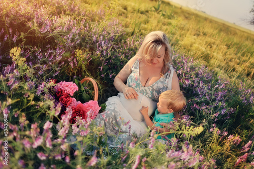 Summer walk on the field with wildflowers pregnant mother with a
