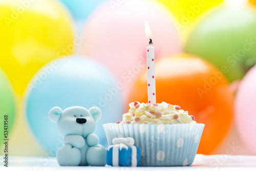 Birthday cupcake with candle and sugar teddy