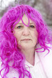 Portrait of an elderly woman in a pink wig
