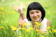 Young woman lying on grass in the field of dandelion