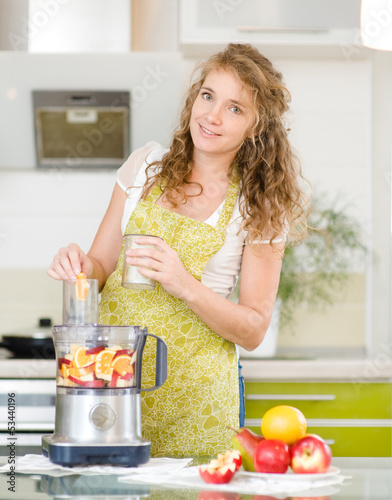 Portrait of a smiling pregnant woman cooking in her kitchen