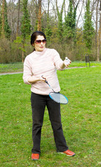 A lovely asian woman playing badminton.